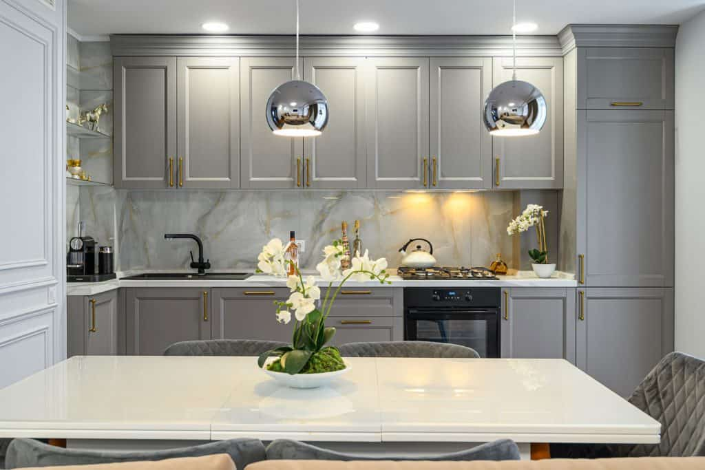 Classic designed kitchen with gray hanging and lower cabinets, white countertop and a kitchen island with flowers