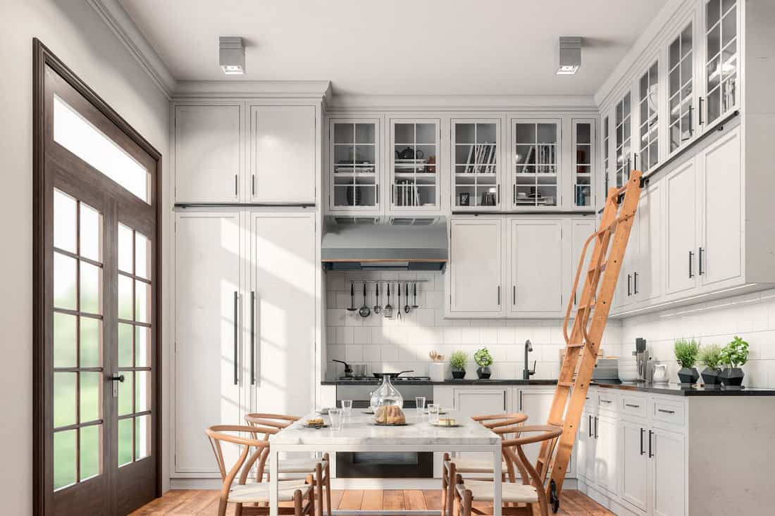 Empty classic kitchen with high cabinets, table, chairs, ladder and decoration with classic windows on the left, How Much Space Between Countertop And Upper Cabinets?