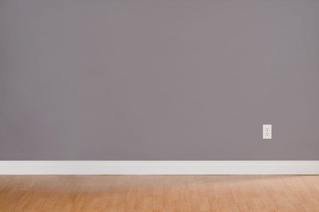 Empty domestic room with wood floors and white moulding. The grey wall has a single wall outlet.