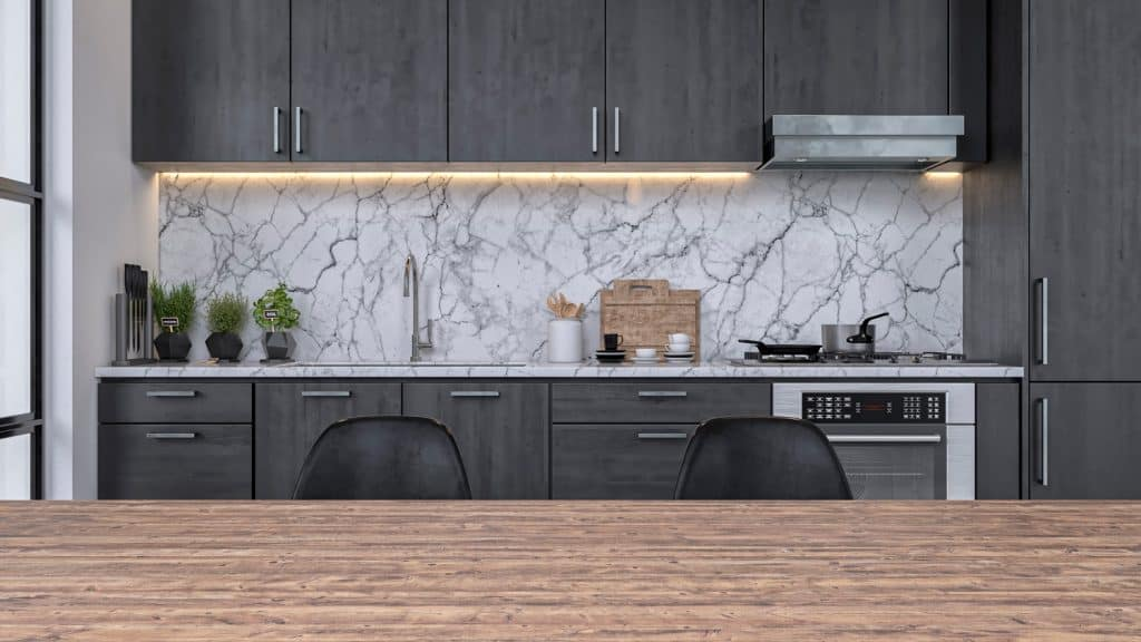 Empty modern kitchen with dark gray wooden kitchen cabinets, white and gray marble background and large hardwood dining table with copy space in the foreground