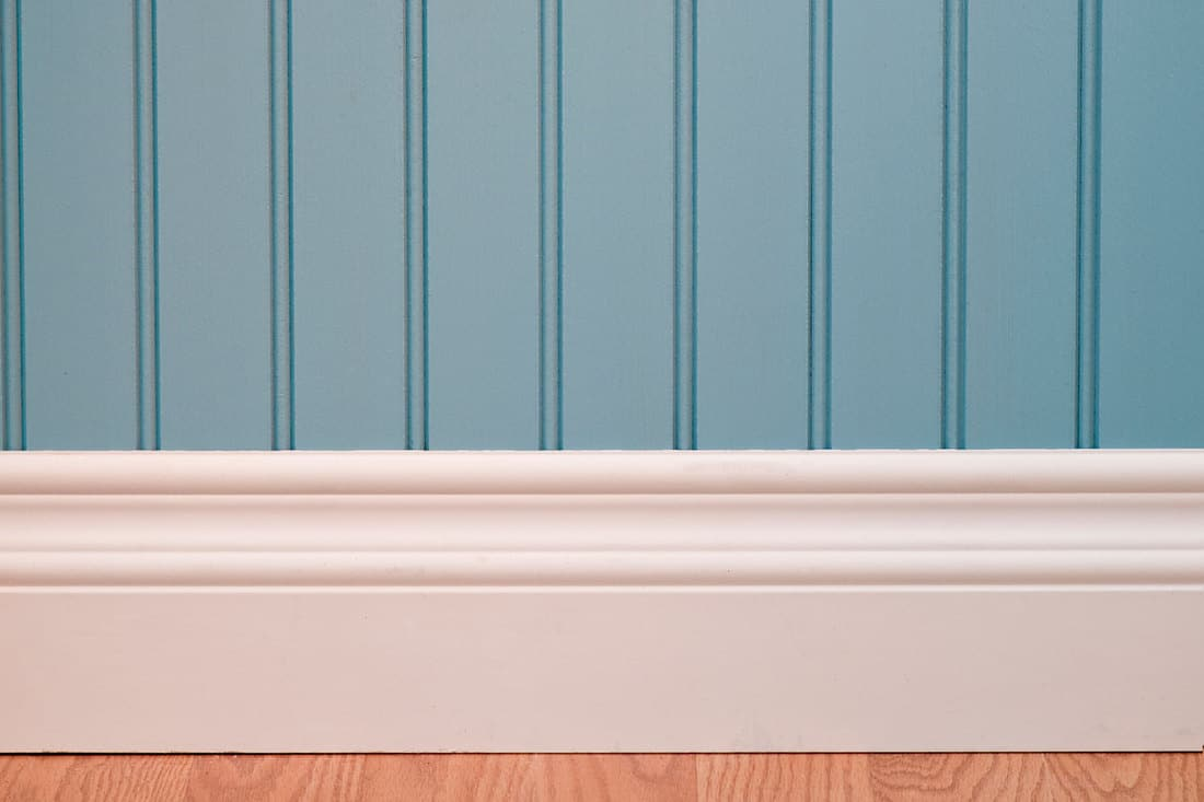 Empty room with power outlet. The wall has a blue beadboard wainscoting and white baseboard, What's The Best Paint Finish For Trim?