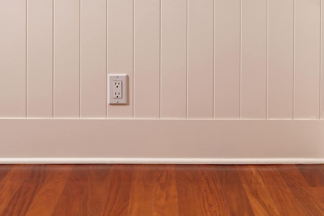 Empty room with power outlet. The wall has a white wainscoting and baseboard