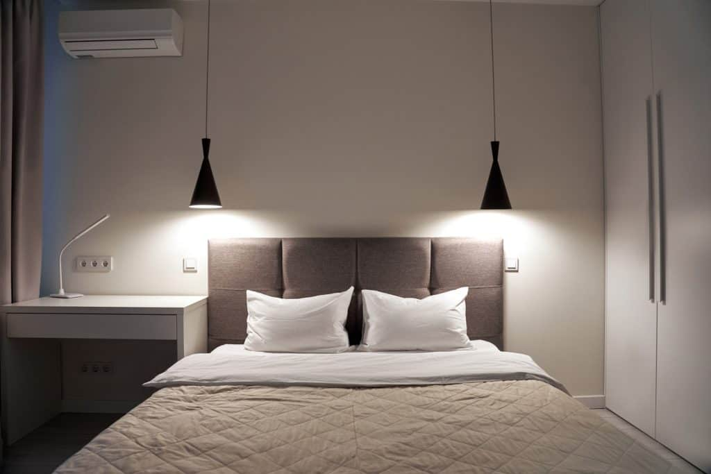 Evening light in comfort and cozy bedroom with modern interior, soft bed, wardrobe, desk table and air condition on grey wall with copy space