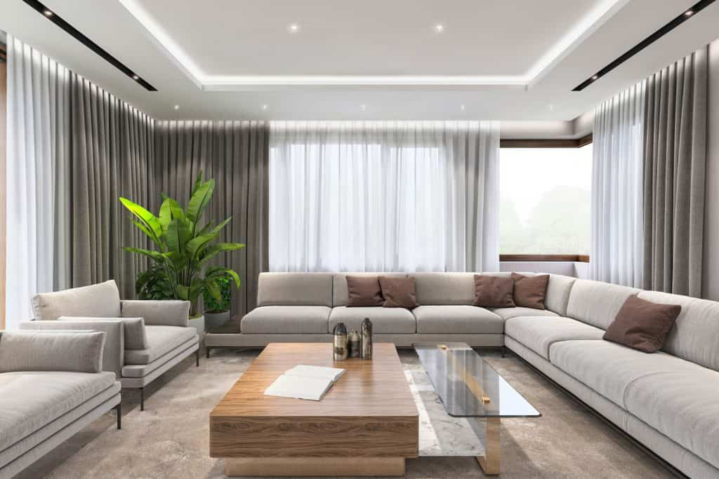 Gorgeous and luxurious living room with huge curtains, long sectional sofas with brown throw pillows