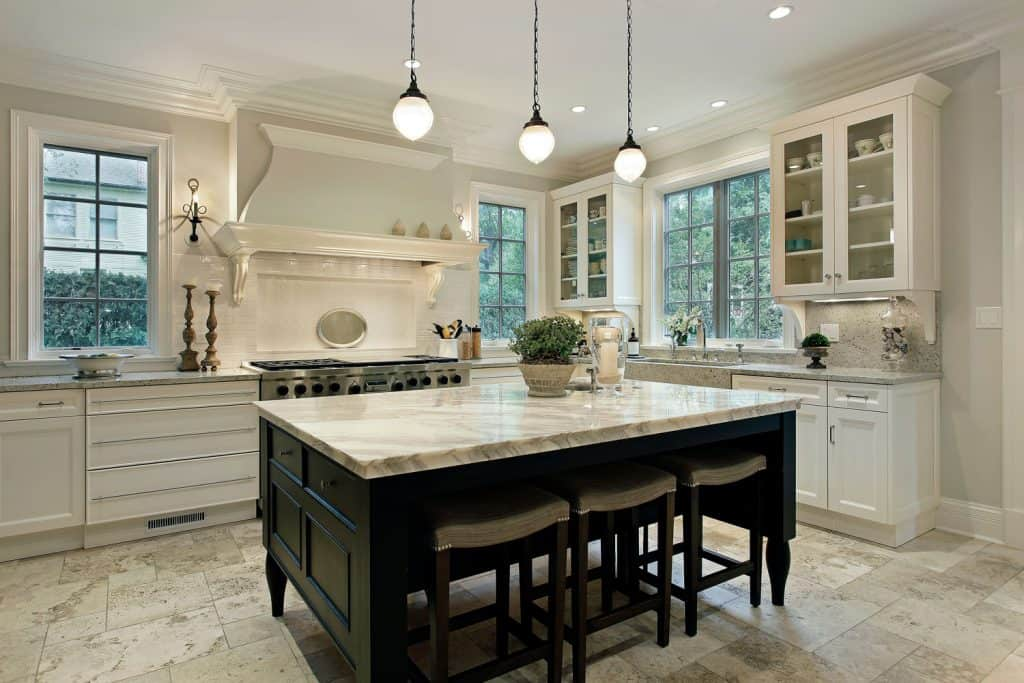 Cream and granite inspired kitchen with white cabinetries and dangling lamps
