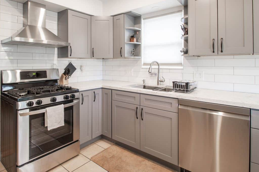 Gray cupboards and cabinets incorporated with cream kitchen countertops
