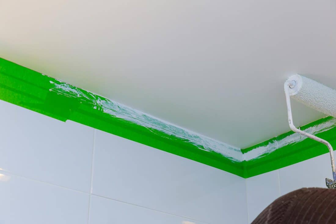 Hand painting ceiling in bathroom painting it with a roller