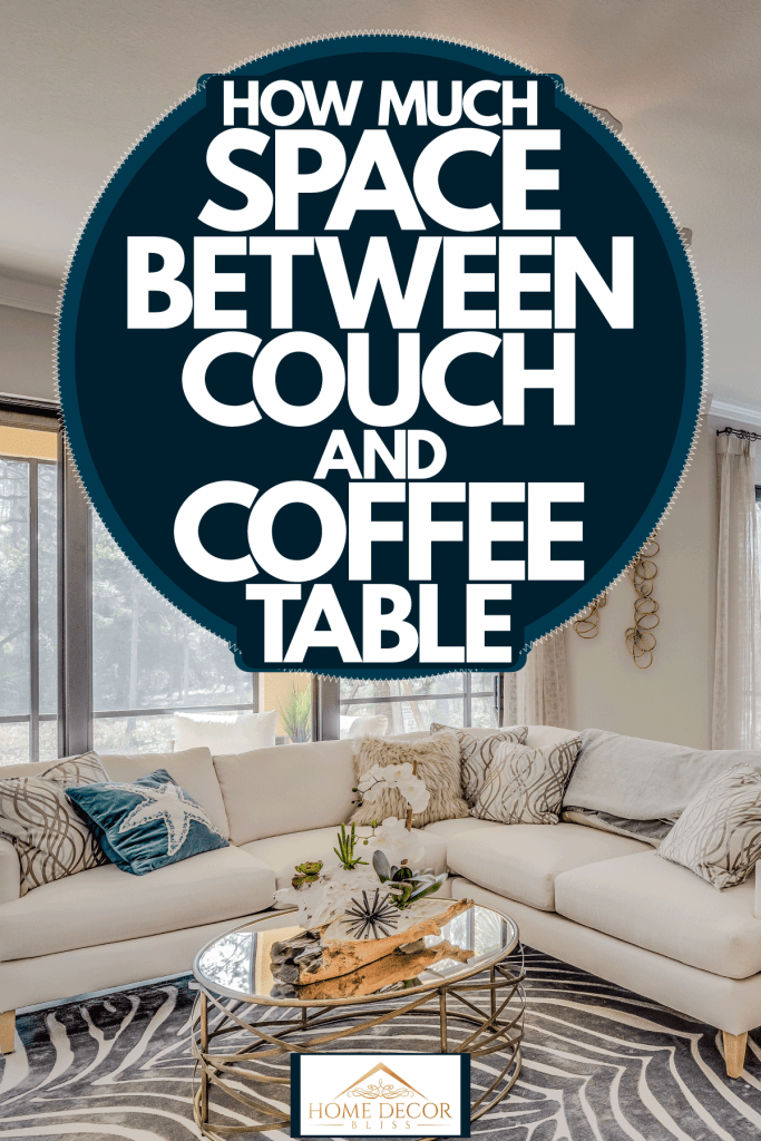 A cozy and living mid century inspired living room with white painted walls, sectional sofa, and a glass coffee table, How Much Space Between Couch And Coffee Table