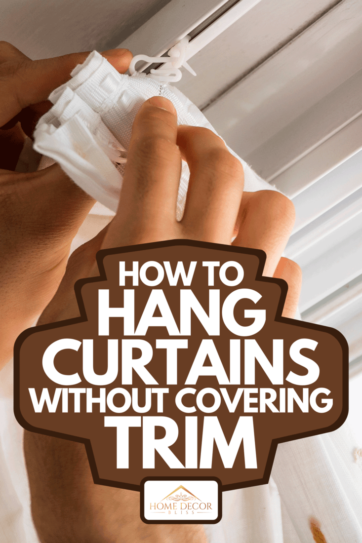 A hands of man installing curtains over window, How To Hang Curtains Without Covering Trim