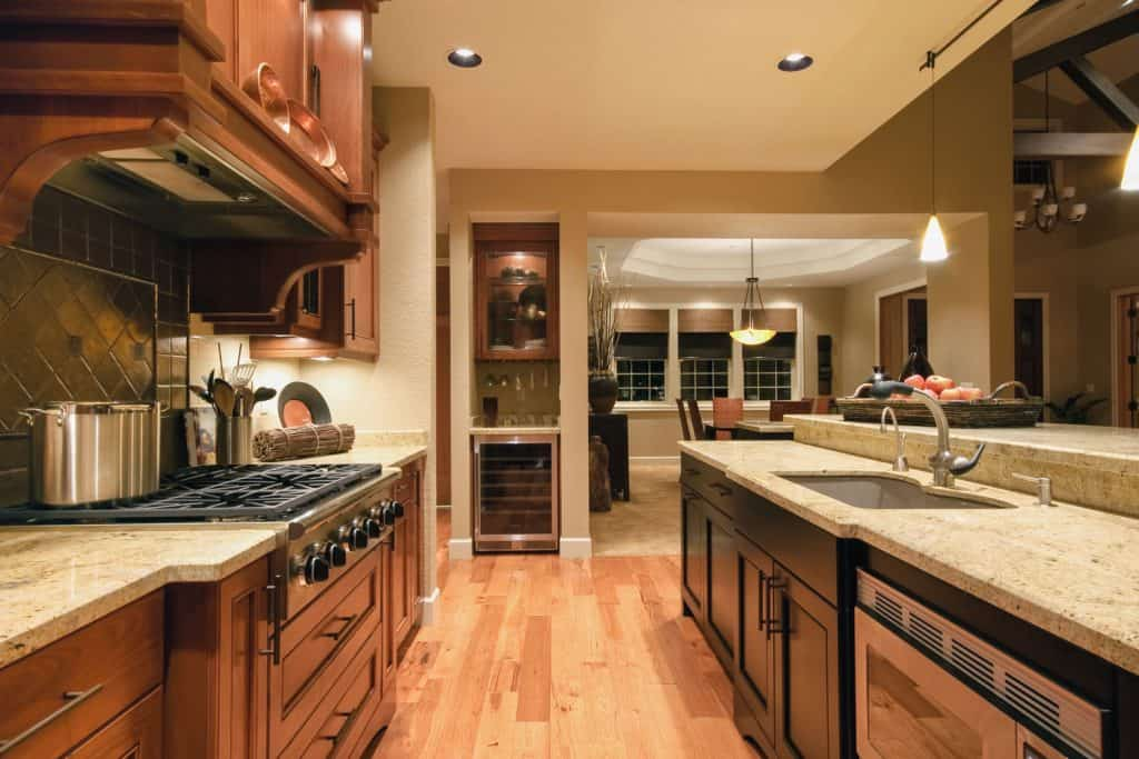 Interior of a rustic kitchen with wooden flooring, oak cabinetries, and a white countertop on the breakfast bar