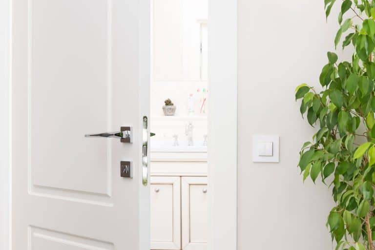 Interior of a white living room with white painted walls and a white door, How To Fix A Cracked Door Or Door Frame