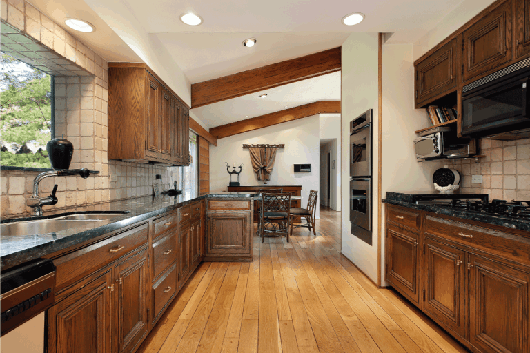 Kitchen with wood cabinetry and oak flooring. What Color Cabinets Go With Oak Floors