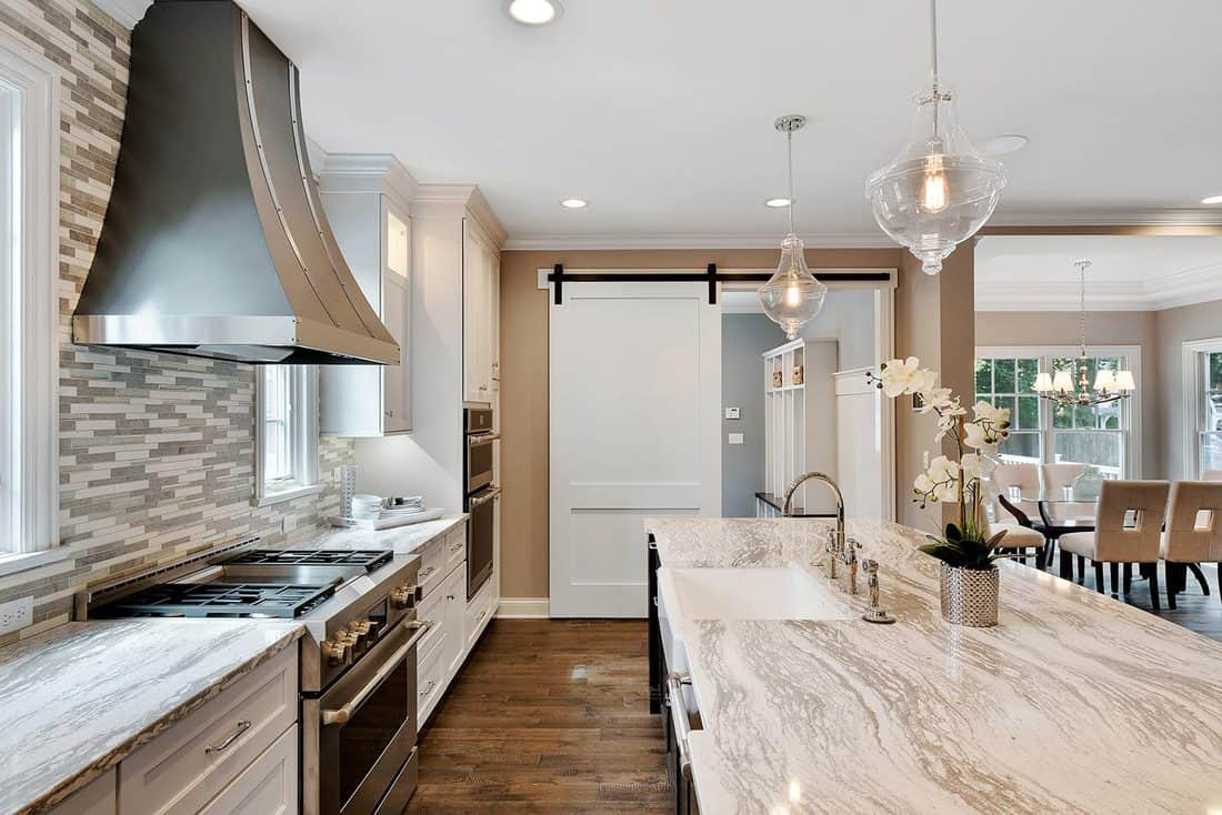 Large vent hood and island in kitchen