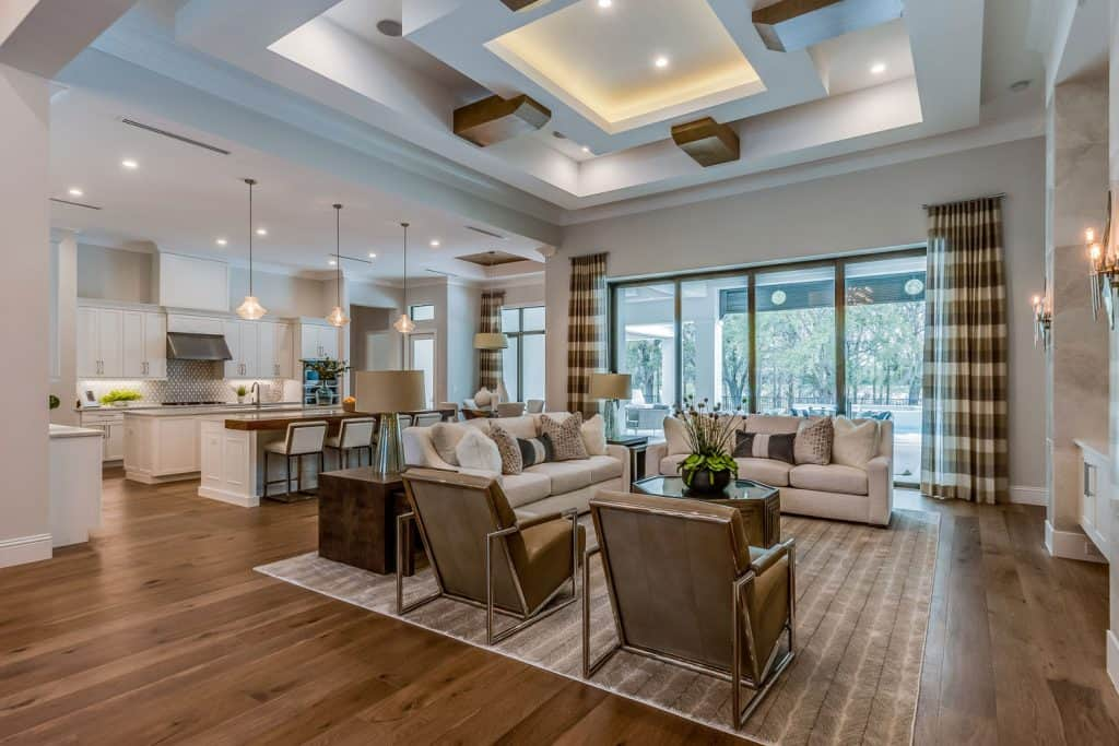 Luxurious living room with recessed lighting, wooden laminated flooring, and dangling lamps on the kitchen area