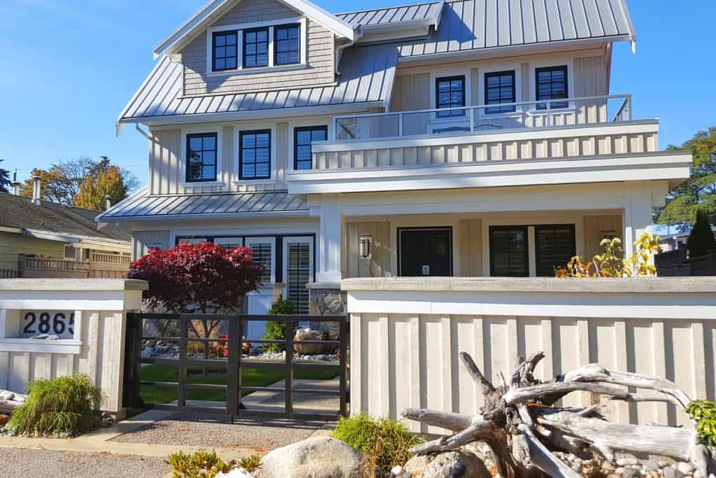Luxurious three storey house with white roofing and a gorgeous gate with gorgeous landscaping
