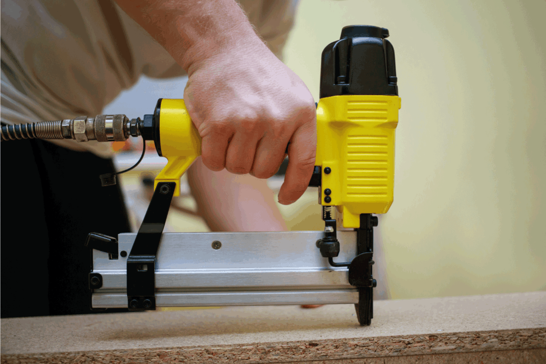 Man working with pneumatic stapler on wood