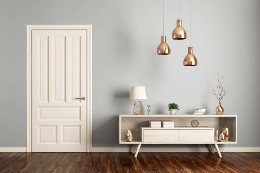 Modern interior living rom with a white door, dangling lamps on the accent chest, and hardwood flooring