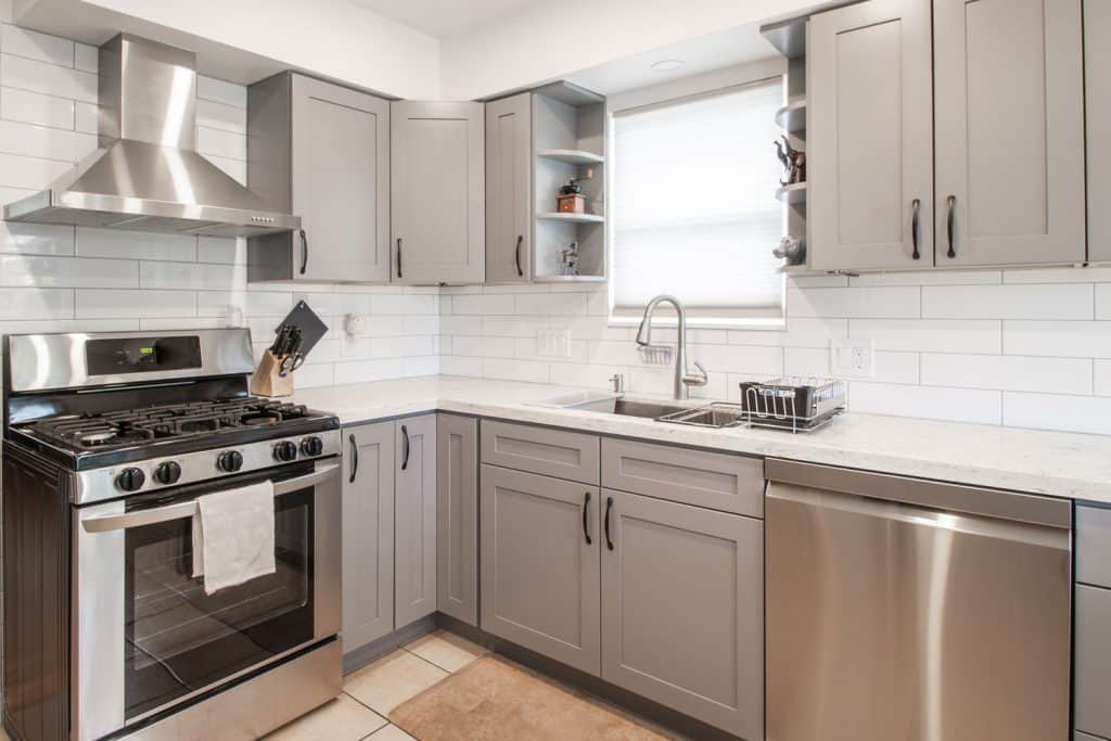 Modern interior of a small rustic and narrow kitchen with white backsplash and gray cabinets and hanging cabinets