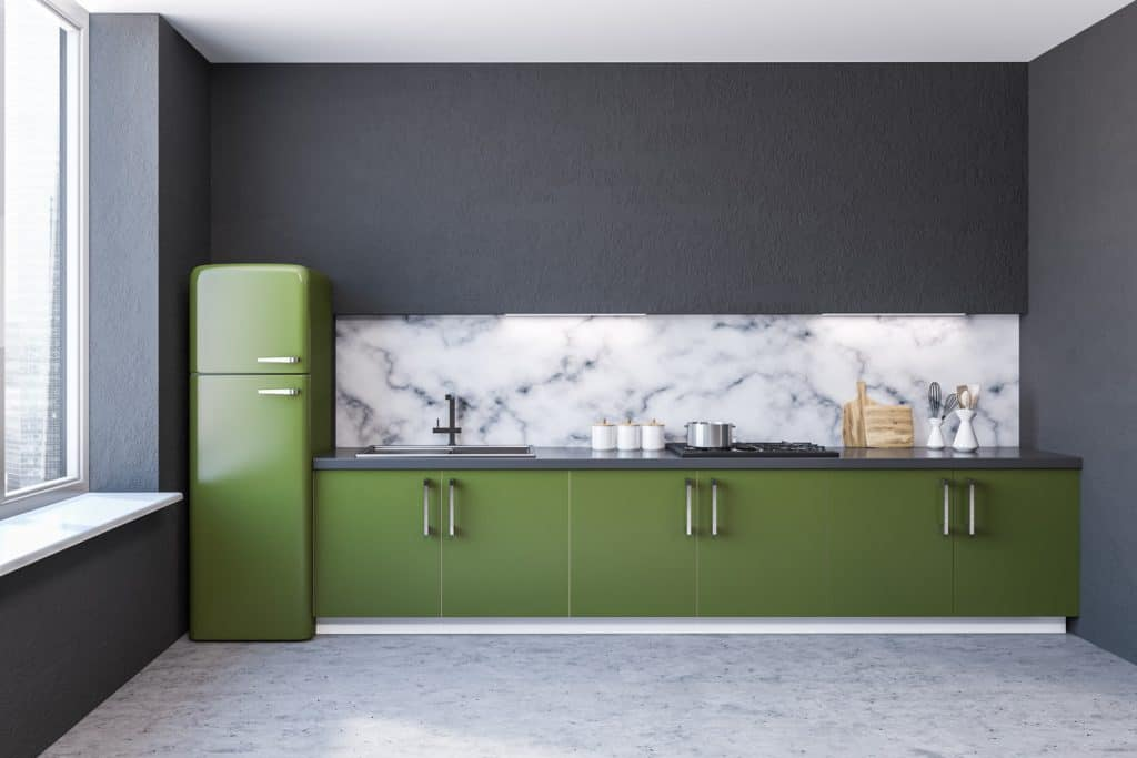 Modern marble wall kitchen interior with large windows, a concrete floor and green countertops with built in appliances