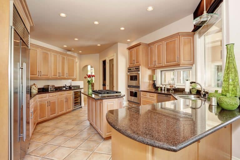Oak cabinetries incorporated with brown marble countertops and recessed lighting, What Color Cabinets Go With Brown Countertops?