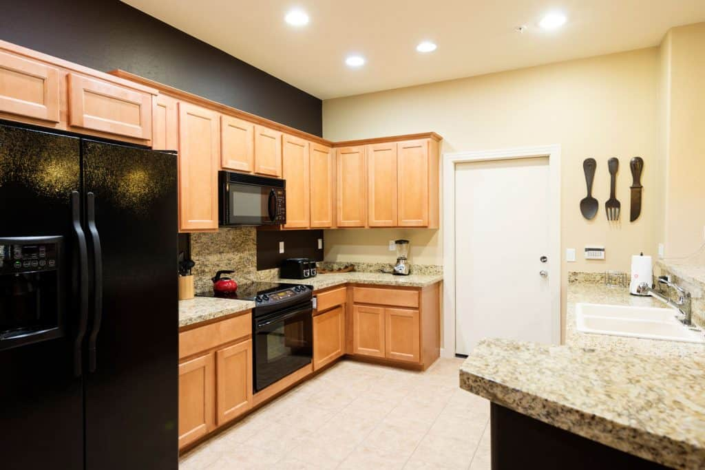 Oak cabinetries inside a rustic kitchen area with recessed lighting