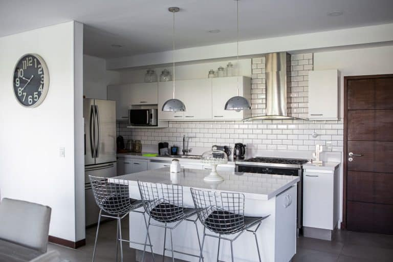 Open space apartment room with white painted walls, white kitchen island with stainless steel chairs and dangling lamps, How Wide Should A Kitchen Island Be?