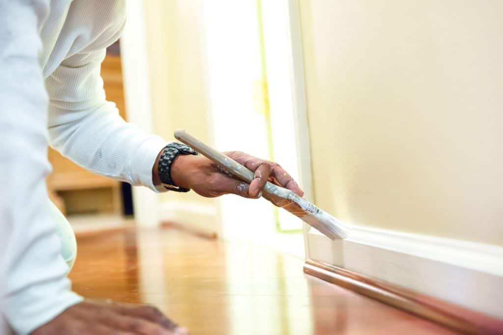 Painter is using a paint brush to paint baseboard in a home