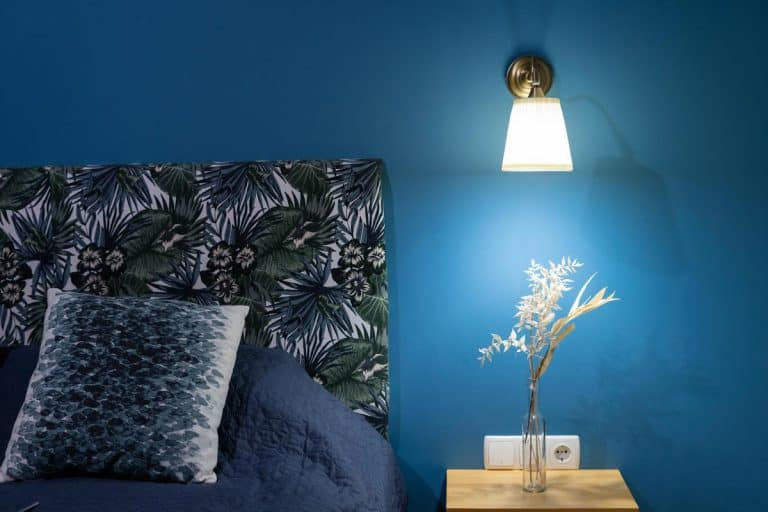 Sconces lamp on blue wall and flowers at nightstand table near comfortable bed, How High Do You Put Bedside Sconces?