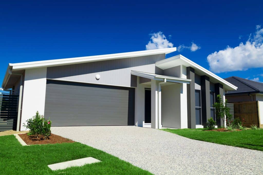 Single storey contemporary house with a pebble driveway and a gray garage door
