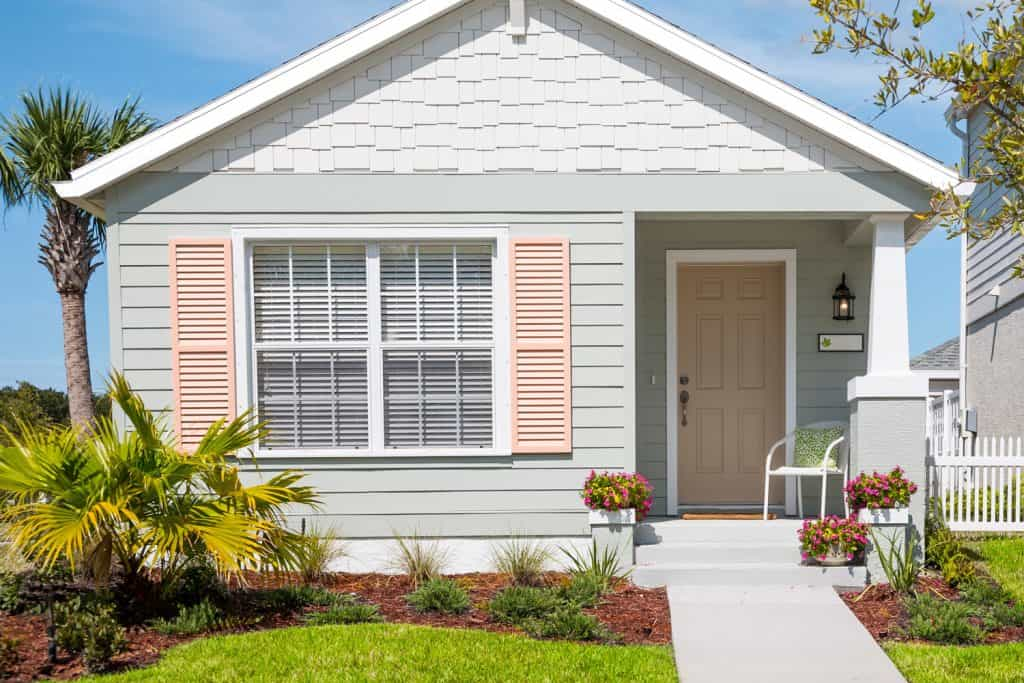 Small cottage with shutters, flowers, front yard and sidewalk, What Color Siding Goes With White Brick?