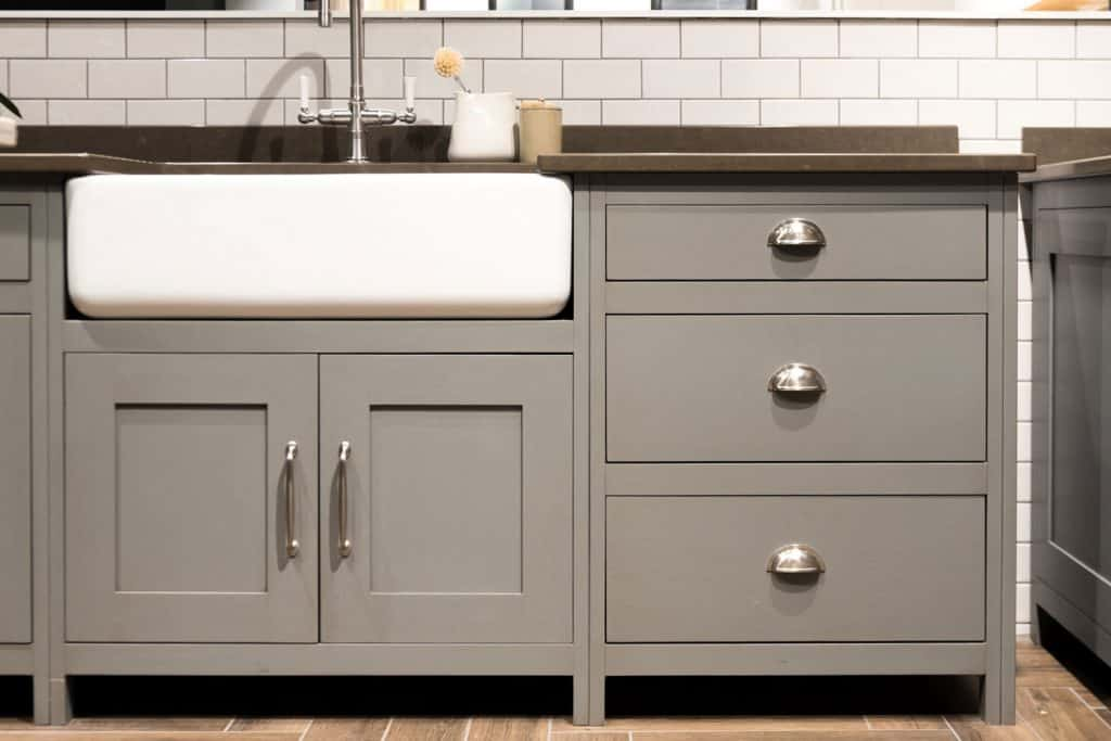 Small cupboards and drawers painted in gray and brown vinyl flooring, What Color Walls Go With Gray Kitchen Cabinets?