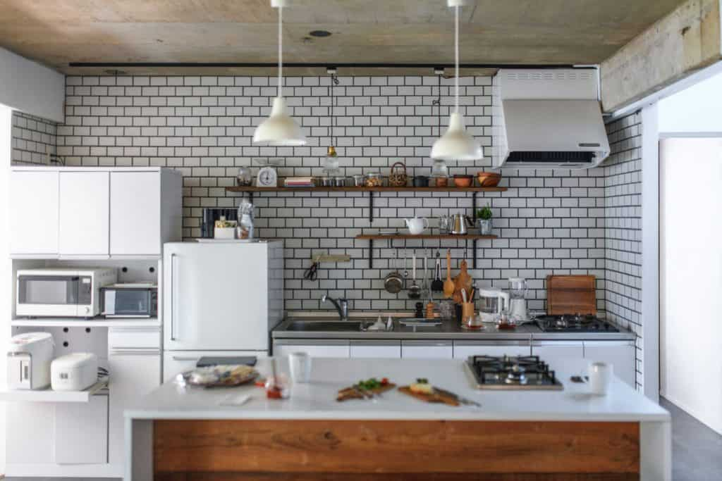 Small rustic inspired kitchen with brick wallpapers on the backsplash and a kitchen island with white dangling lamps