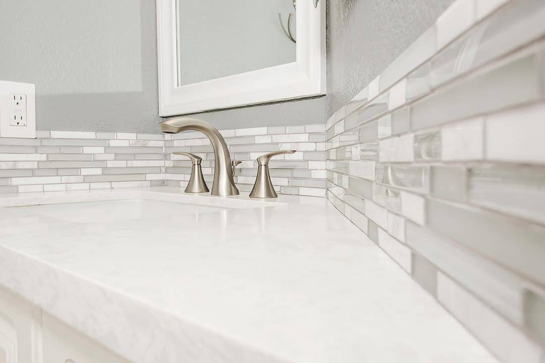 The detail of a newly remodeled bathroom faucet and counter