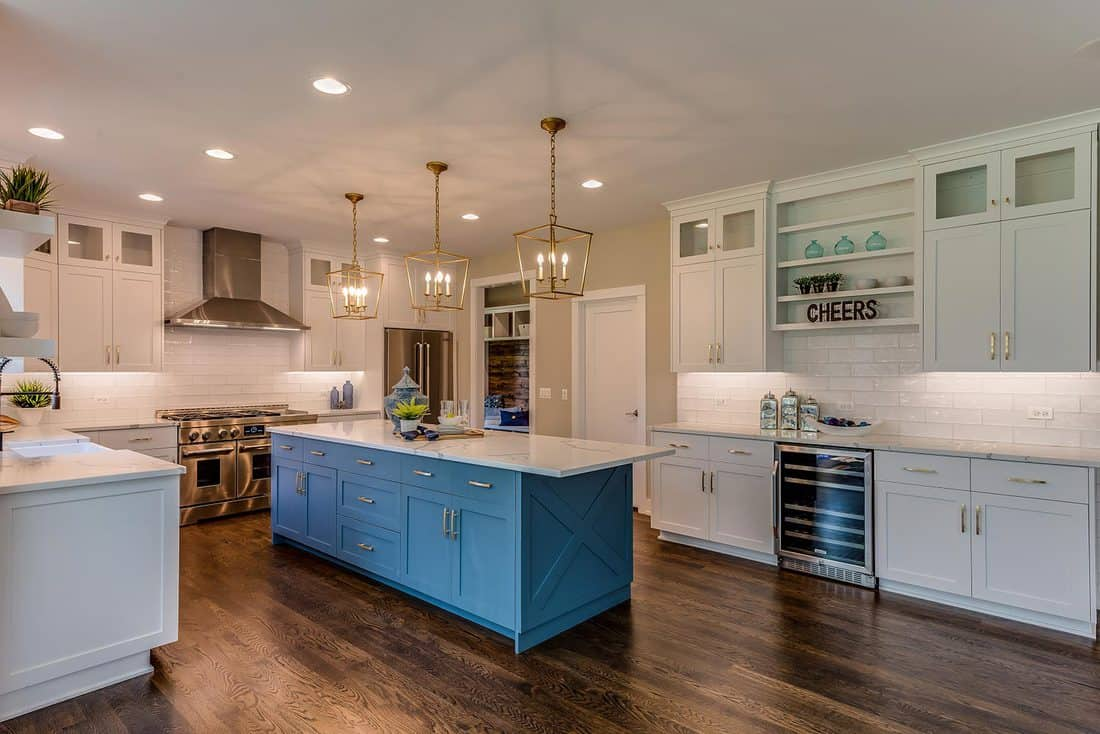 Three pendant lights hang over kitchen island surrounded by dark brown hardwood floors