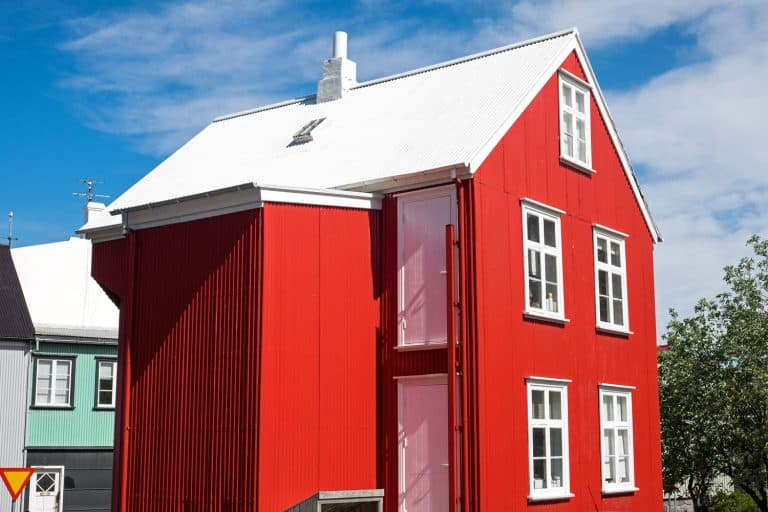 Two storey barnhouse style residential home painted in red with white window trims and white roofing, What Color House Goes With A White Roof?
