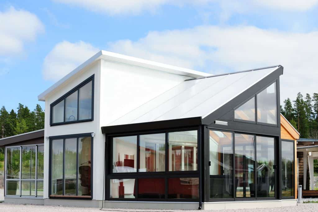 Two storey contemporary house with huge glass windows and white painted roofing