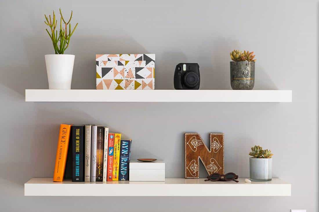 Two white painted modern bookshelves with books, plants, a decorative storage box and personal items