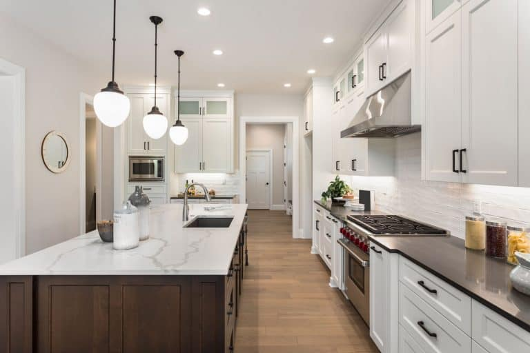 Ultra modern kitchen with recessed and dangling lamps on the kitchen island with white granite countertop, What Types Of Countertops Are Cheaper Than Granite?