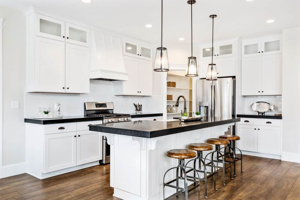 Ultra modern and luxurious interior of a kitchen with white cupboards and cabinets incorporated with black countertops
