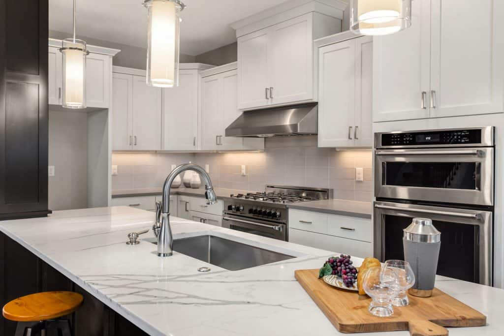 White cabinetries with silver handles and a white granite countertop on the kitchen island