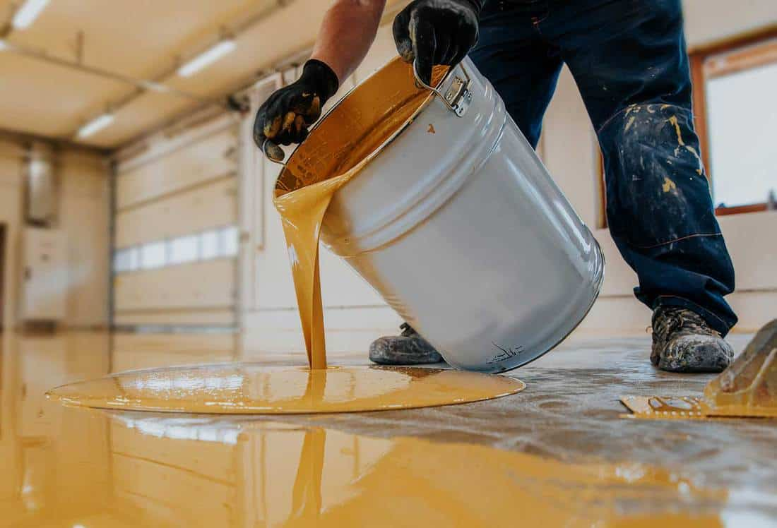 Worker applying a yellow epoxy resin bucket on floor for the final coat