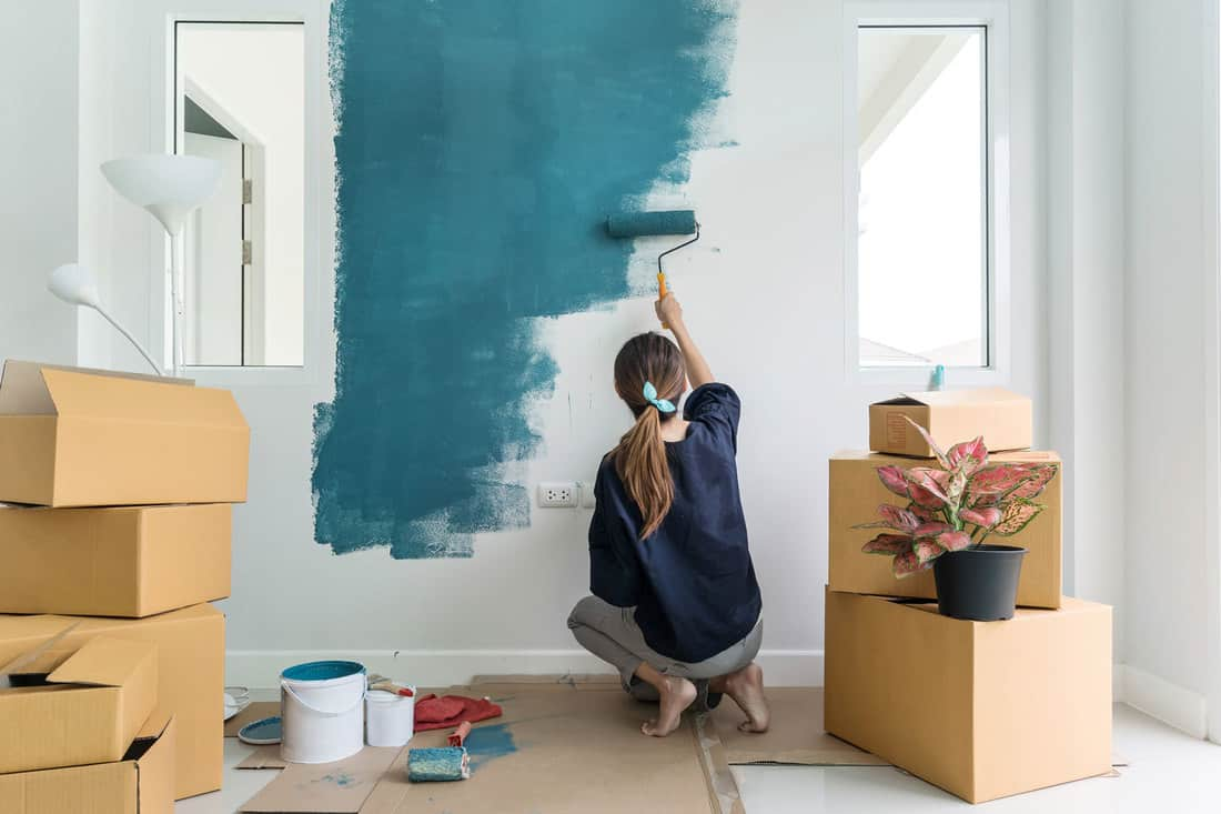 Young asian happy woman painting interior wall with paint roller in new house, How Long Should Benjamin Moore Paint Dry Between Coats?