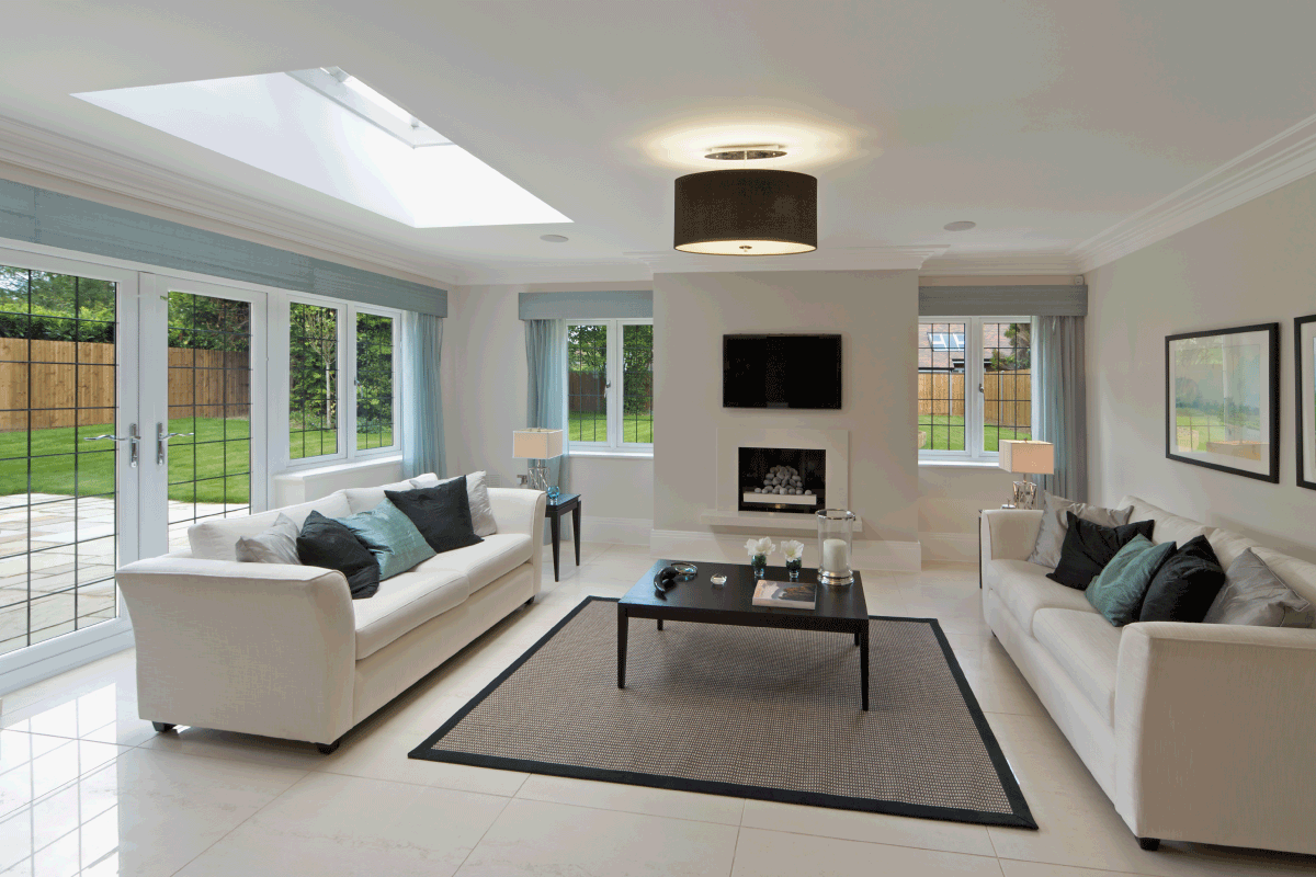 a slightly angled view of a bright and spacious lounge in an expensive new home with large leaded glass windows. How Much Space Between Furniture For Walking