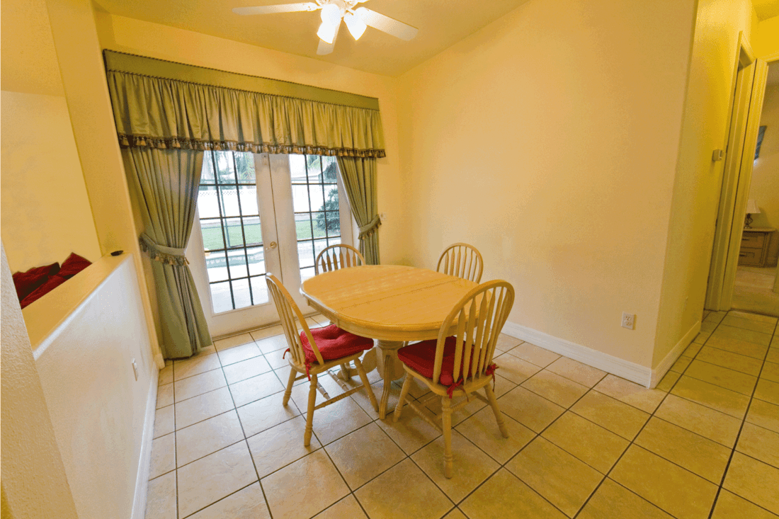 back to basic breaktast nook with simple table and chairs beside a large window with curtain