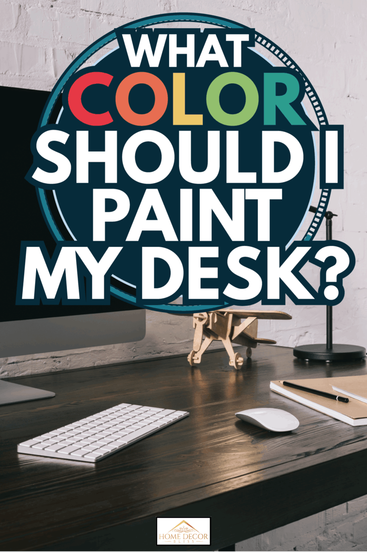 black wood desk with small wooden airplane figurine, computer mouse, keyboard, and monitor. What Color Should I Paint My Desk