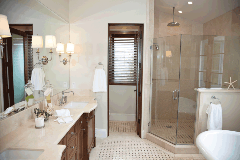 bright bathroom with sconce lighting, brown accents, glass shower area. What Is The Best Color Temperature For Bathroom Lighting