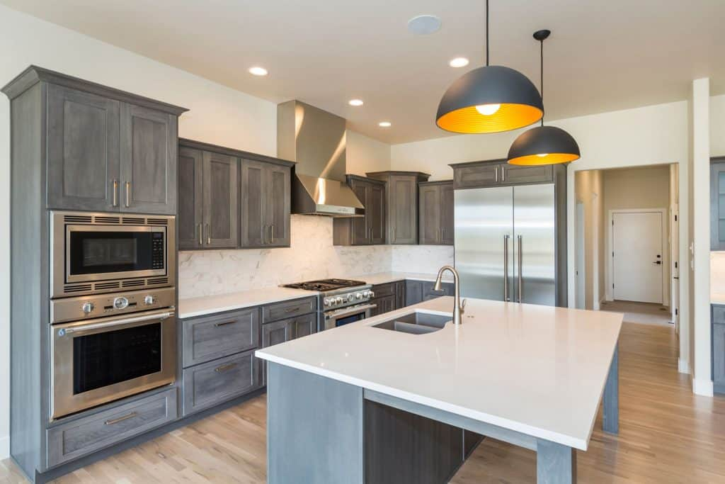 Interior of a luxurious and modern kitchen with vinyl flooring and dangling lamps on the kitchen island