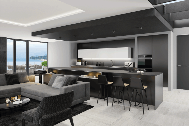living room interior and modern minimalist kitchen with big kitchen island and three stools. Matte black cabinets. Black carpet. Grey sofa with armchairs. What Color Walls Go With Black Ceiling