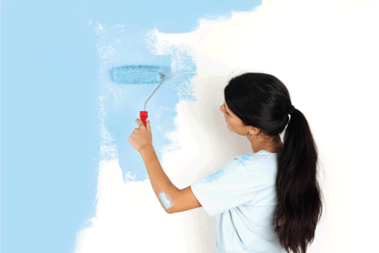 roller in woman hand paint on the wall. Sherwin Williams Emerald Vs Duration Which To Choose