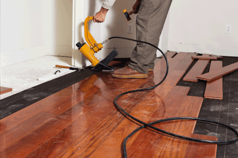 A worker installing hardwood floor in an American upscale home using a pneumatic nail gun. What Type And Size Of Nails For Hardwood Floors